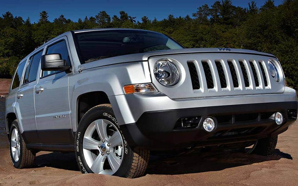 Silver Jeep Patriot with trees behind it