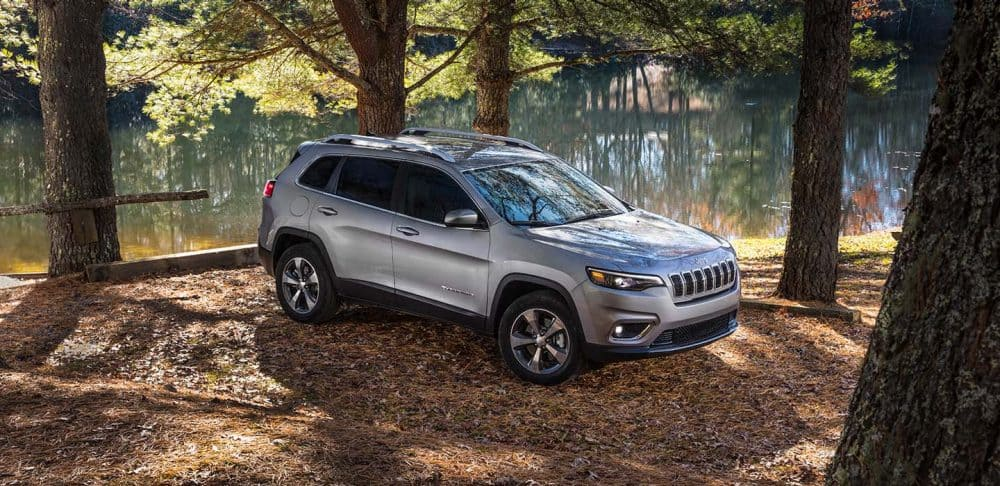 White 2019 Jeep Cherokee off-road in woods by river