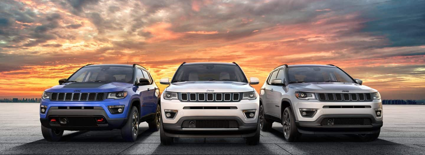 Three 2019 Jeep Compass models pose against a sunset backdrop