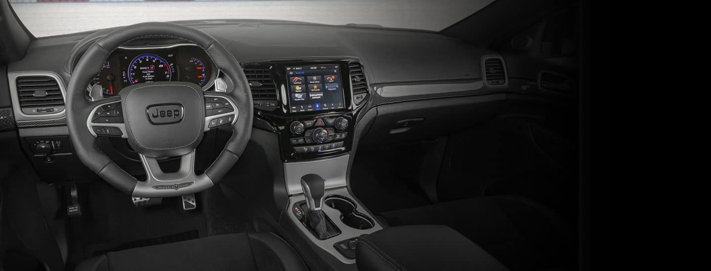 Grand Cherokee interior with the cluster display and Uconnect touchscreen on.