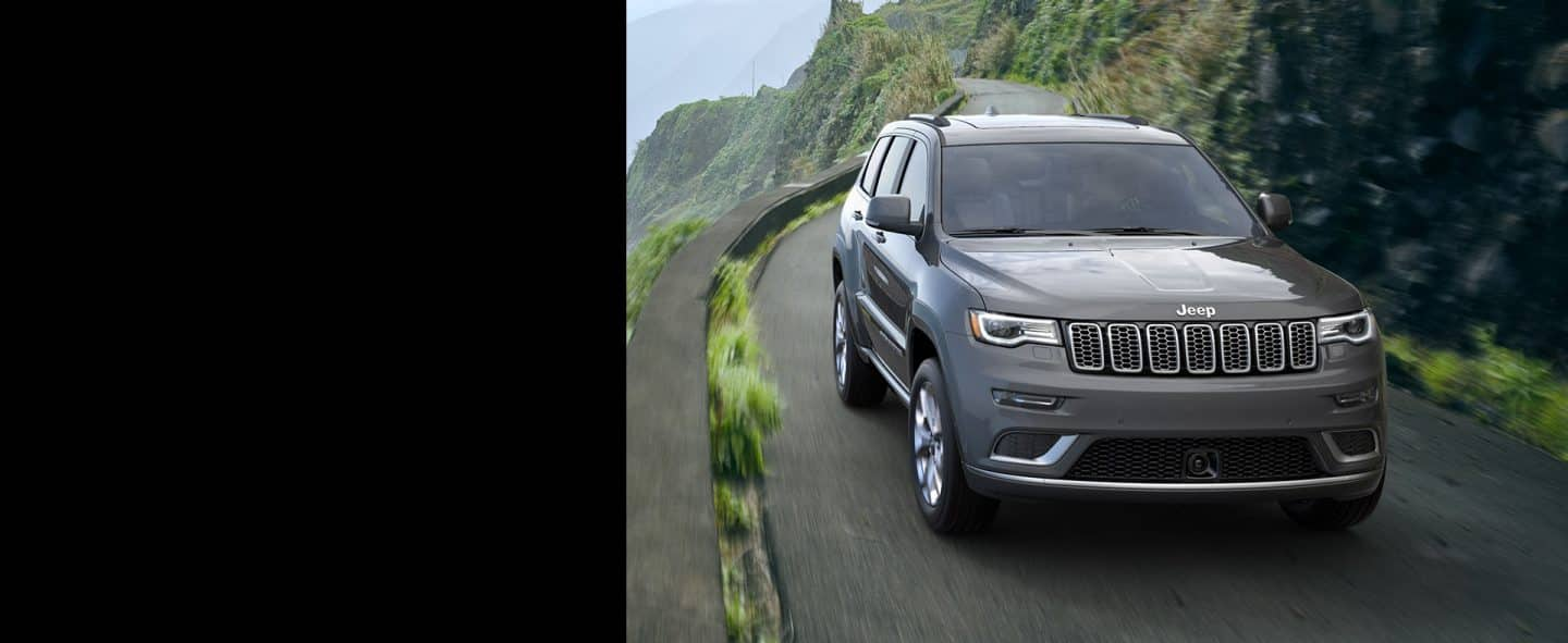 Jeep Grand Cherokee being driven on a highway in the mountains.