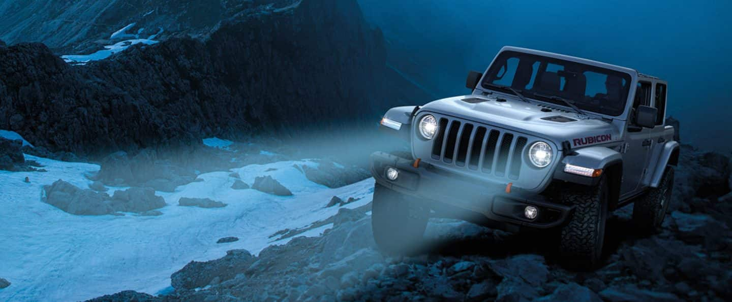 Jeep Wrangler with headlamps illuminated.