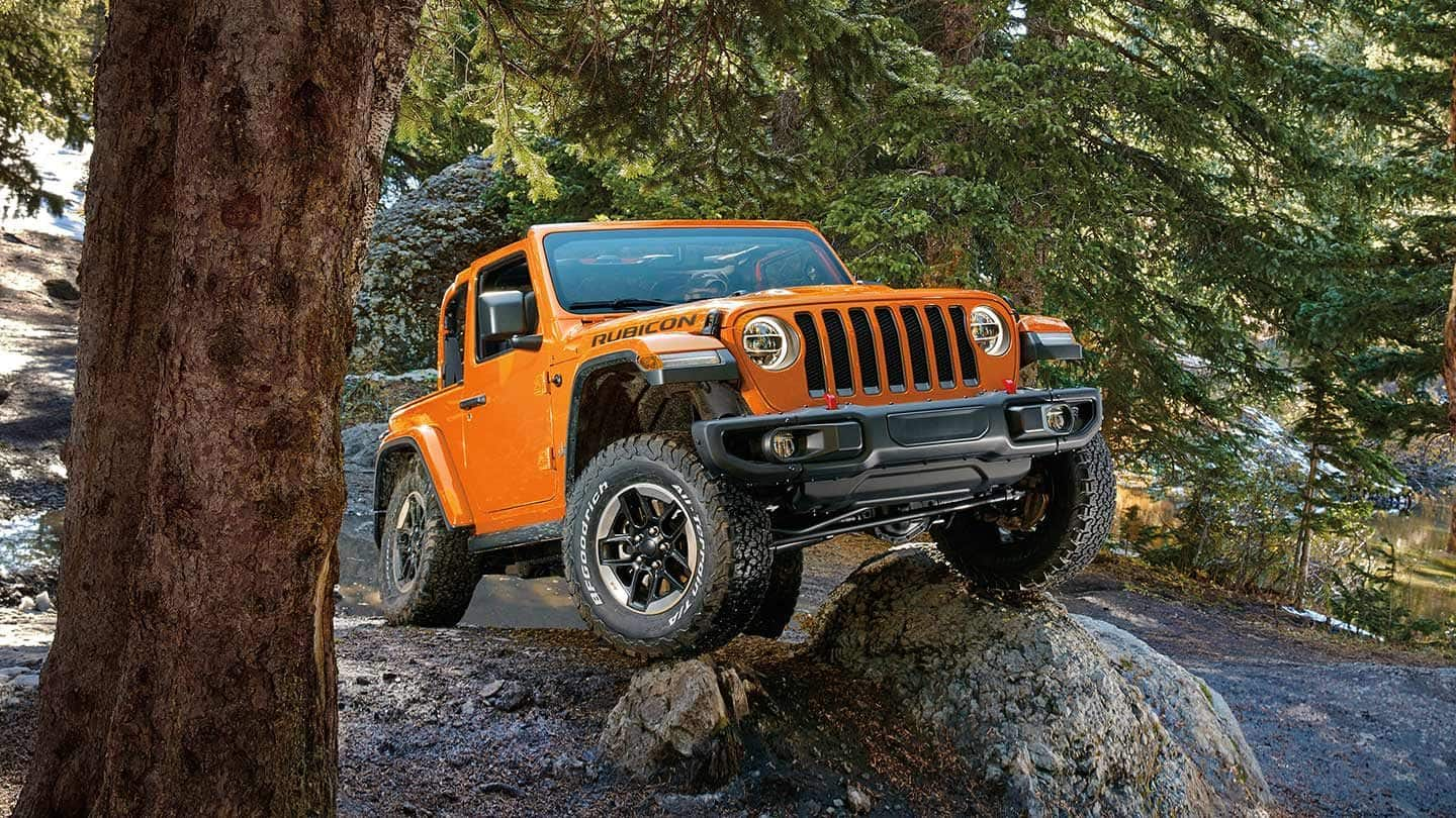 Jeep Wrangler driving on rocky terrain.