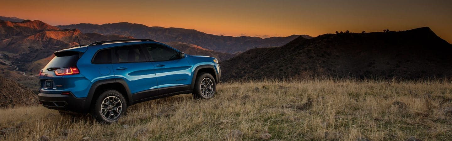 A blue 2020 Jeep® Cherokee Trailhawk parked on a grassy hill in the mountains at sunset.