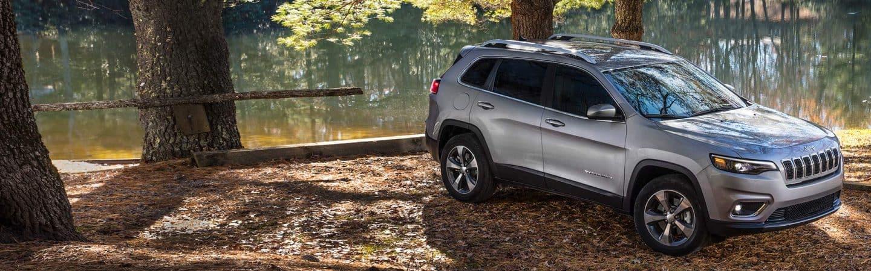 UnJeep® Cherokee Limited2020 plateado en un estacionamiento con árboles y un lago de fondo.