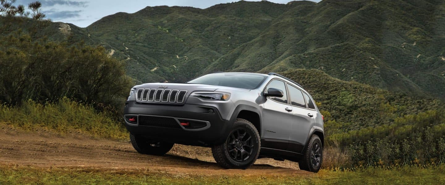 A gray 2020 Jeep Cherokee Trailhawk parked on a mountainous dirt path.