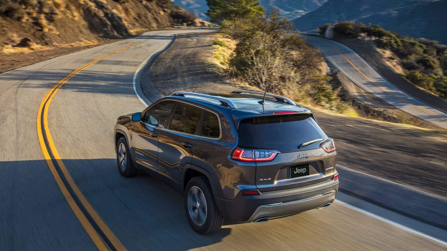 Display A 2020 Jeep Cherokee Limited being driven on a winding mountain road.