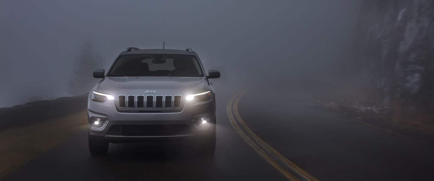 The 2020 Jeep Cherokee Limited on a foggy road at dusk with its headlamps and fog lamps lit.