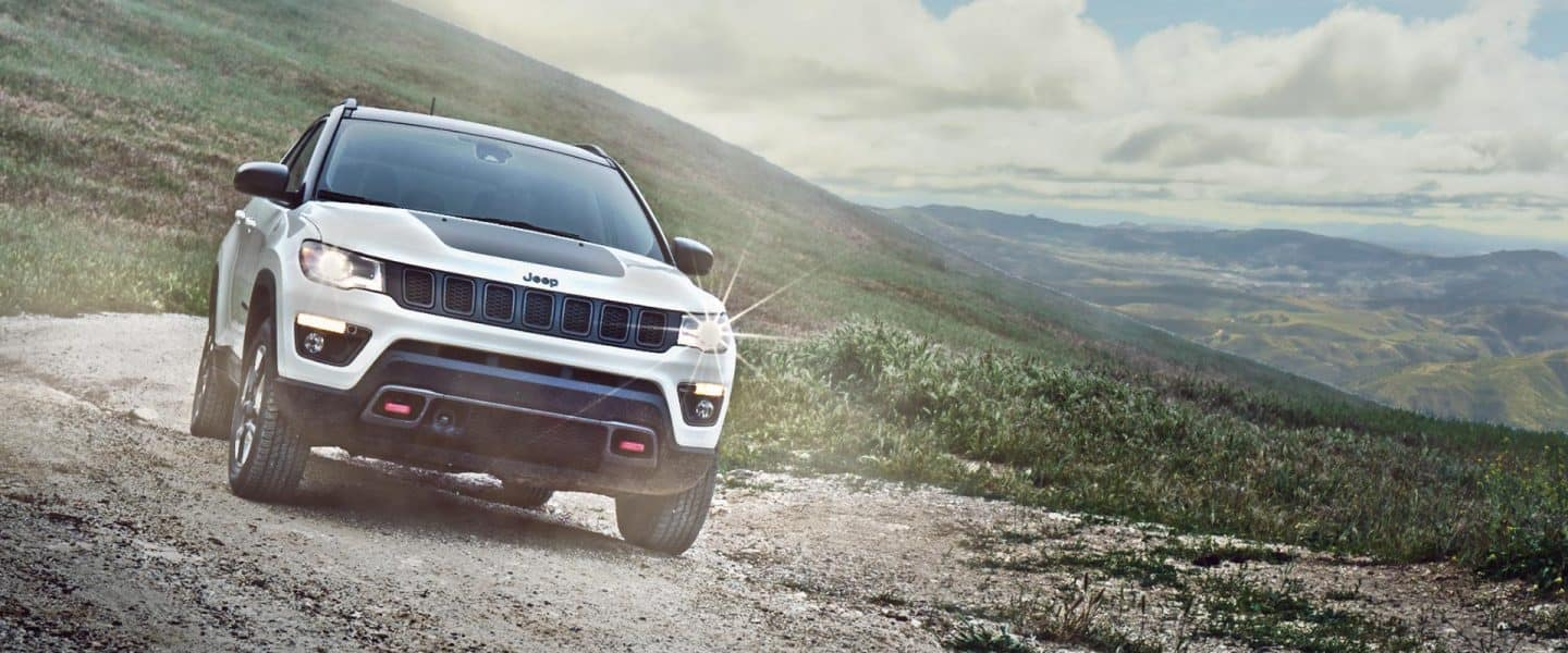 The 2020 Jeep Compass parked on a gravel track on a mountain.