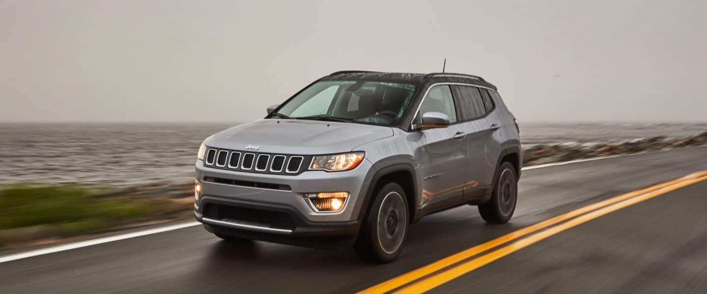 The 2020 Jeep Compass being driven on a rainy road by the lake.