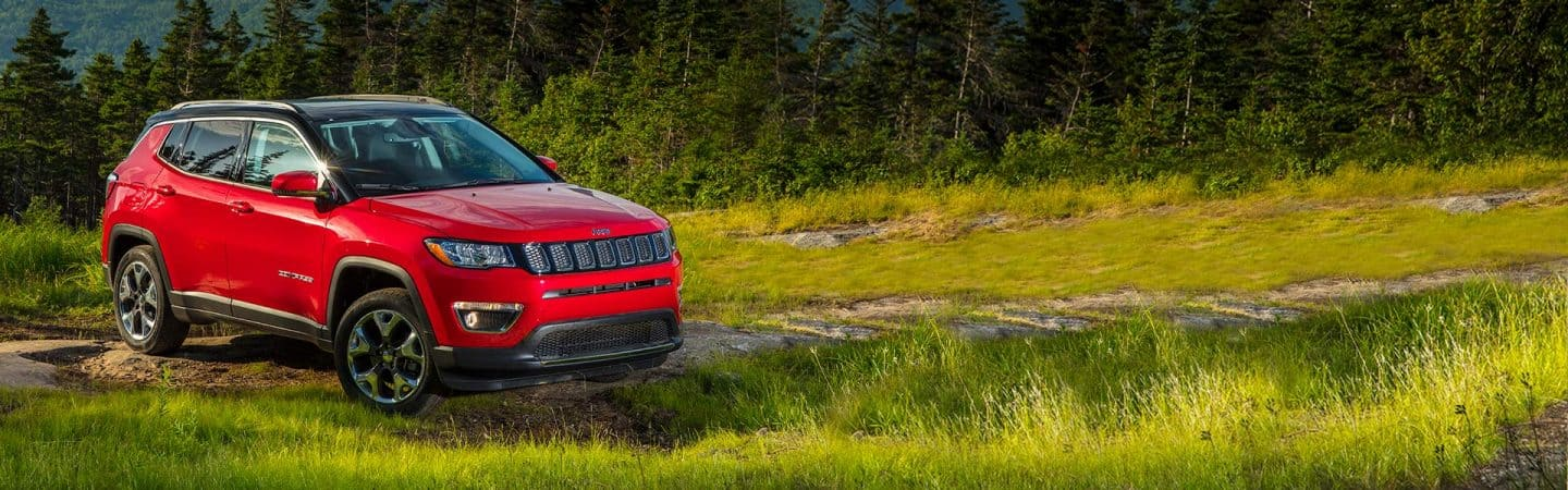 A red 2020 Jeep® Compass Limited parked off-road, in a mountainous, wooded area.