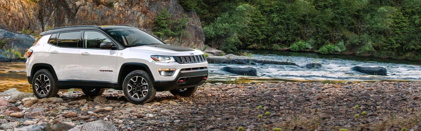 A white 2020 Jeep® Compass Trailhawk parked on a stoney bank, next to a flowing stream in a mountainous, wooded area.