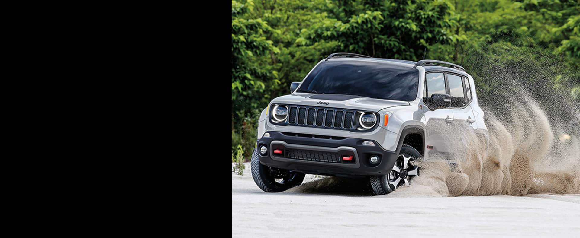 The wheels of 2020 Jeep Renegade throw up sand as it is driven on the beach.