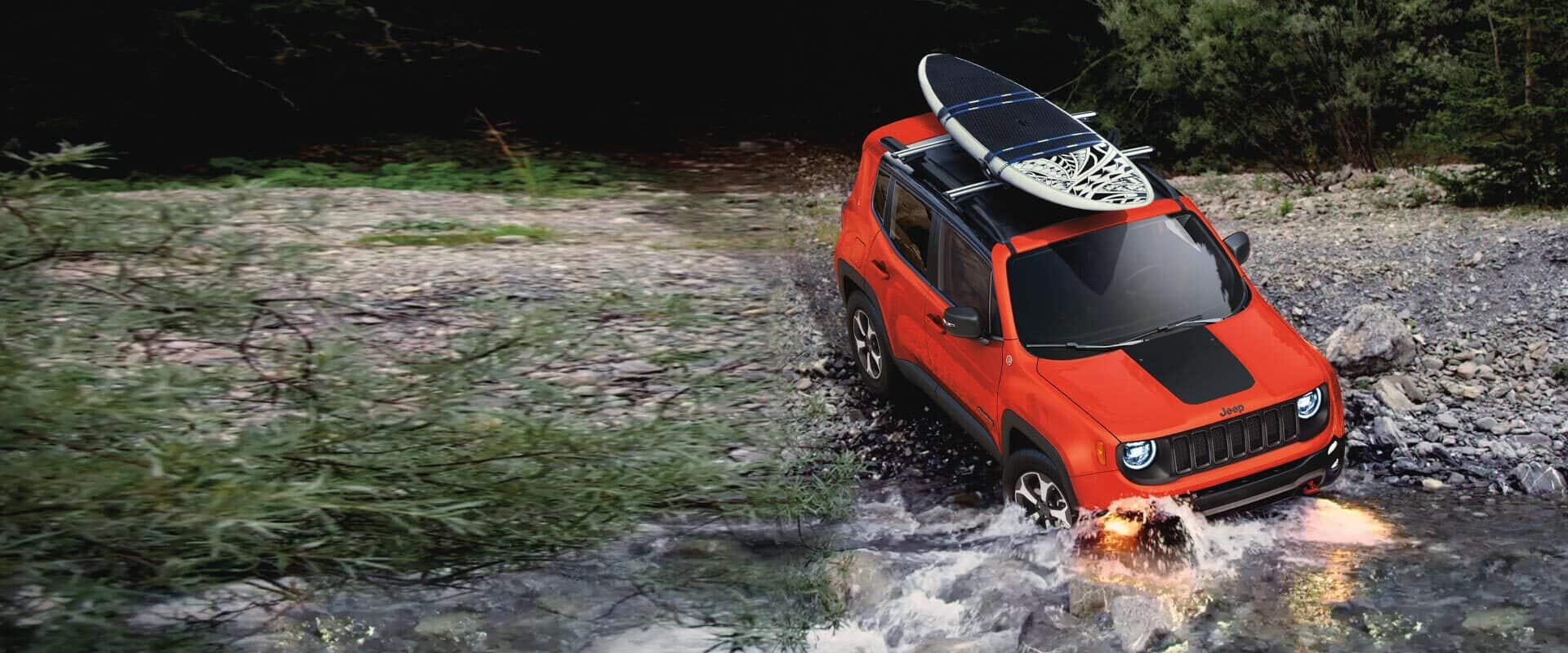 The 2020 Jeep Renegade fording a shallow stream with a surfboard attached to its roof rack.