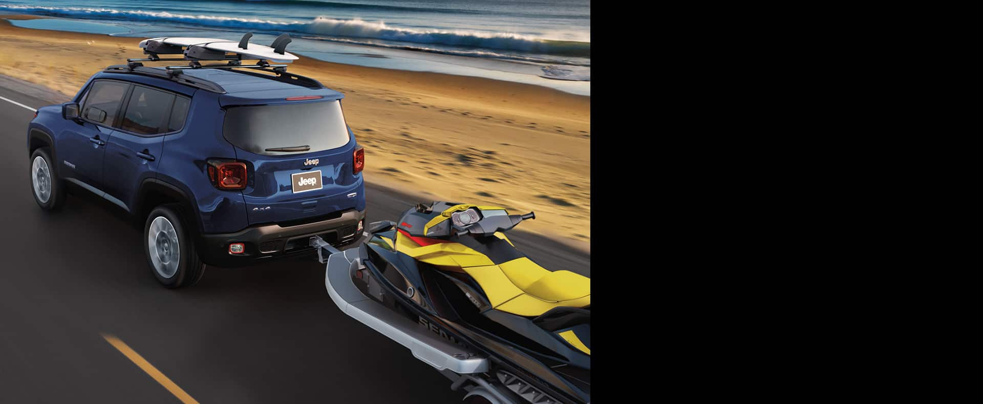 2020 Jeep Renegade tows an ATV and carries a surfboard on its roof rack as it is driven on a beachside road.