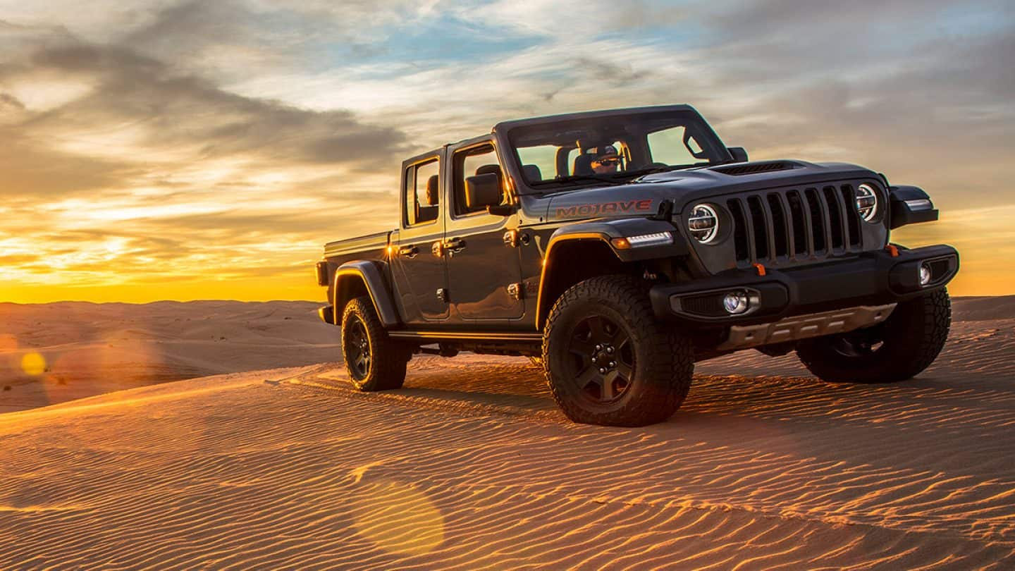 Display The 2021 Jeep Gladiator Mojave parked on a large dune in the desert at sunset.