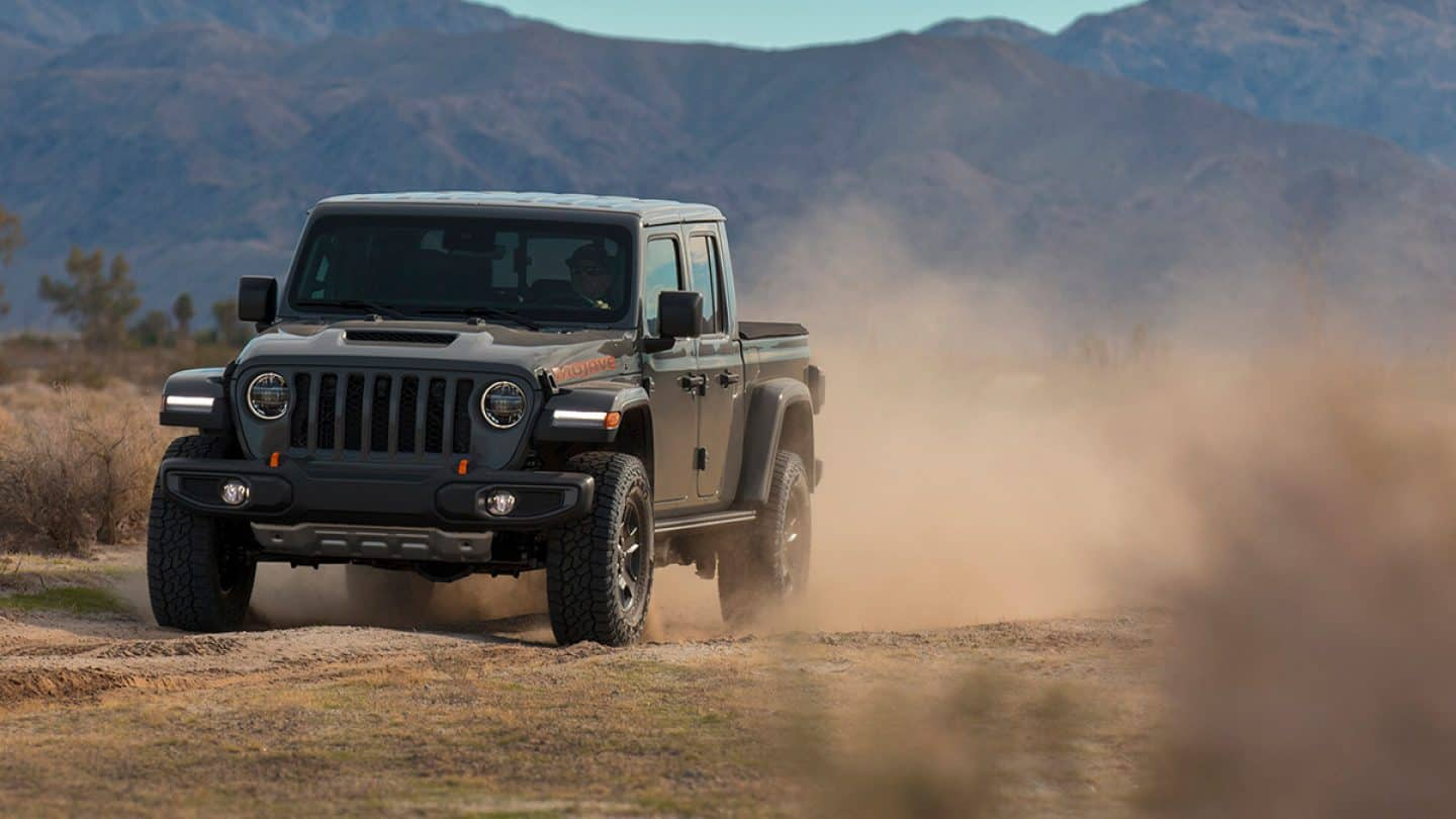 Display The 2021 Jeep Gladiator Mojave being driven on a trail in the mountains, kicking up a cloud of dust.