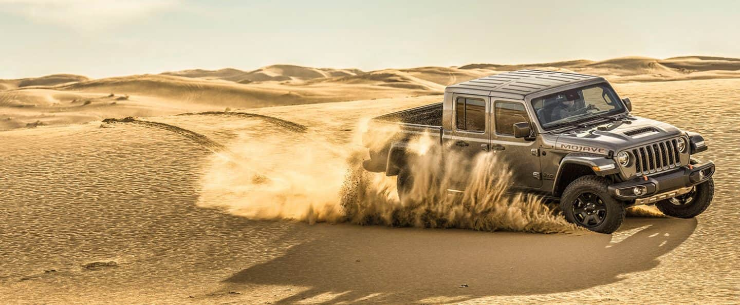 The 2020 Jeep Gladiator Mojave churning up sand as it is driven through the desert.