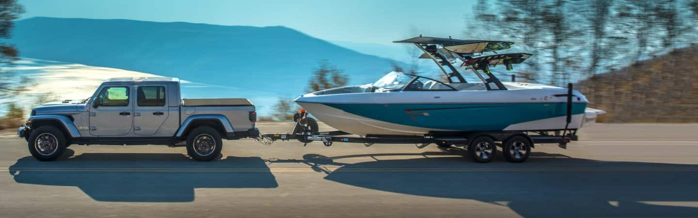 A silver 2020 Jeep® Gladiator Overland towing a boat on a lakefront highway near the mountains.