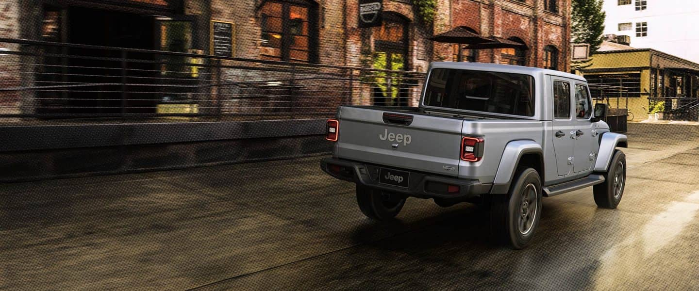Grey gladiator driving on a rainy street