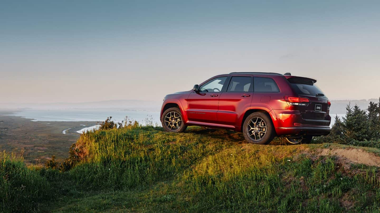 Display A three-quarter side view of the 2020 Jeep Grand Cherokee Limited X parked on a hill overlooking a body of water.
