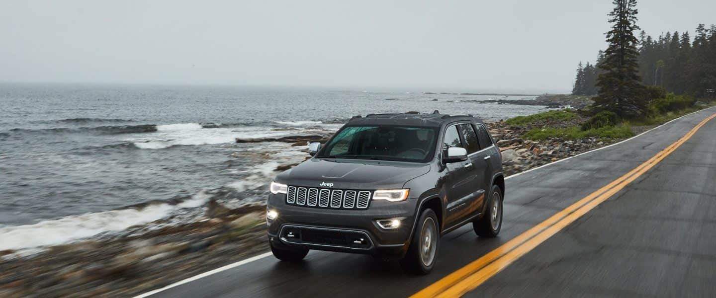 The 2020 Jeep Grand Cherokee being driven along a seaside highway.