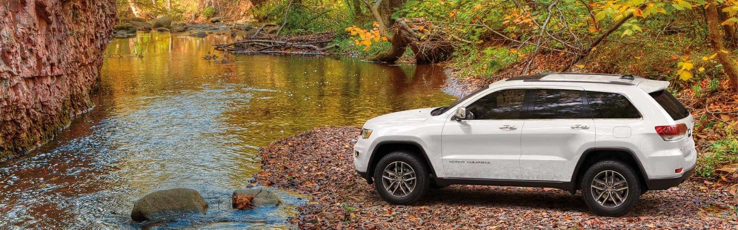 A white 2020 Jeep® Grand Cherokee Limited parked facing a stream with trees and a rock wall in the background.