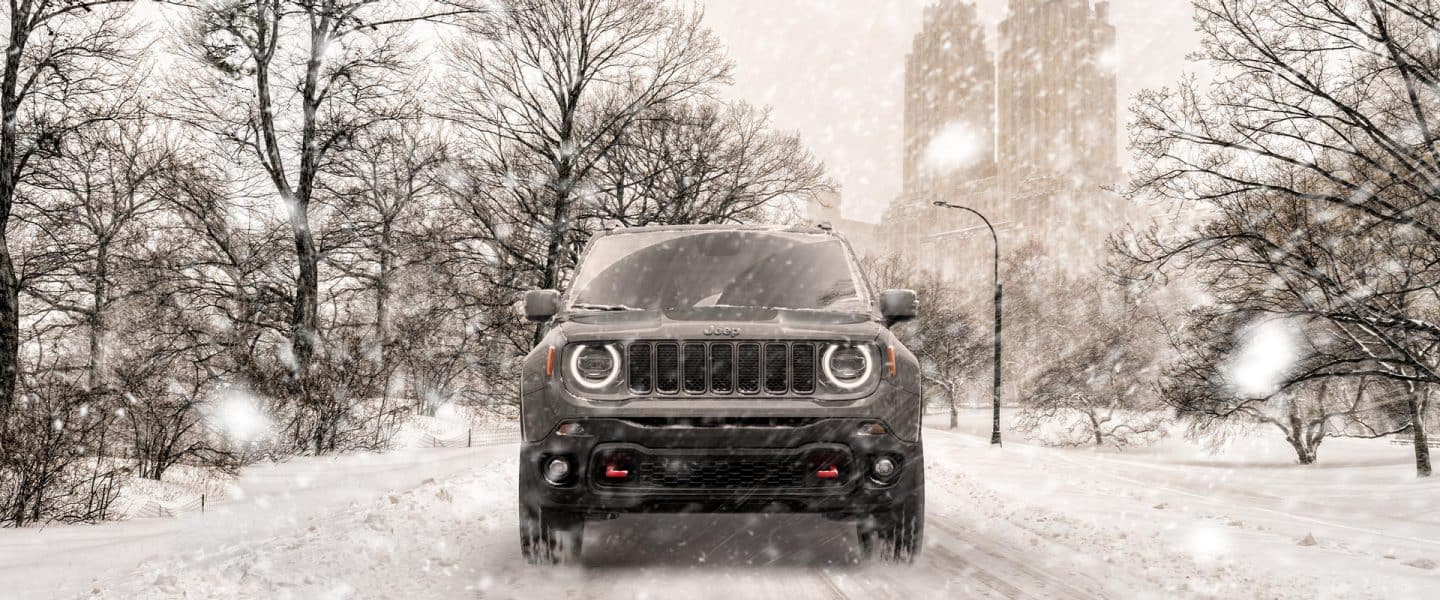 A 2020 Jeep Renegade being driven through a snowstorm on a city street.