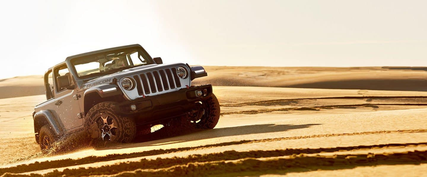 A 2020 Jeep Wrangler Rubicon with its top off, being driven on sand.