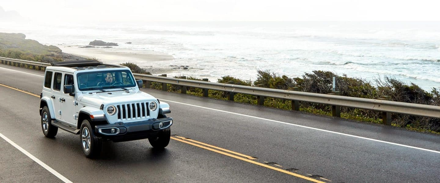 A white 2020 Jeep Wrangler Sahara on a road beside the water.