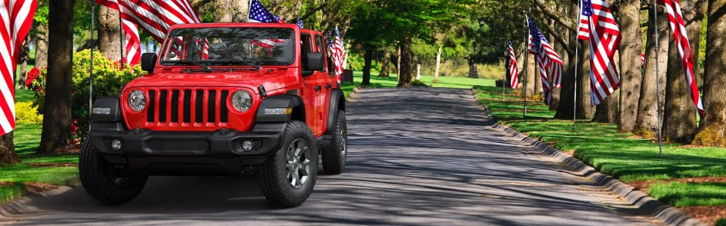 The 2020 Jeep® Wrangler Freedom Edition parked on a street flanked by a row of American flags.