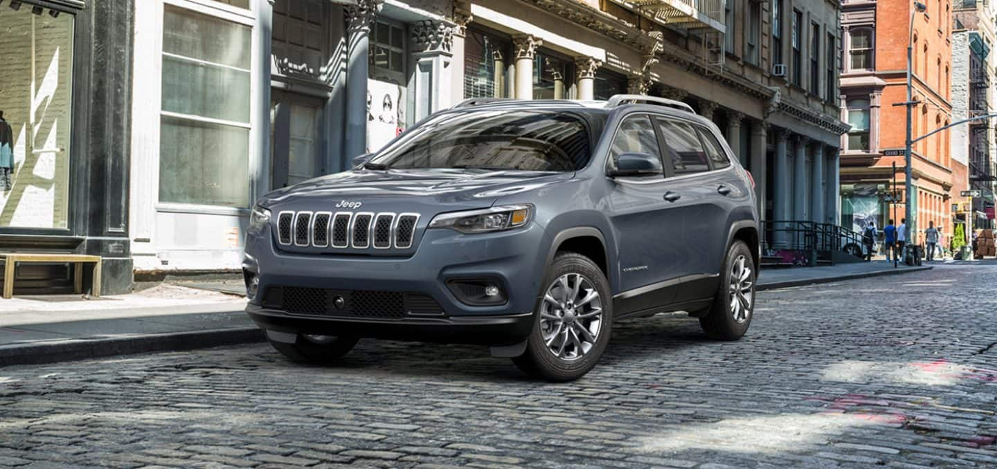 Display The 2021 Jeep Cherokee parked on a cobblestone street.
