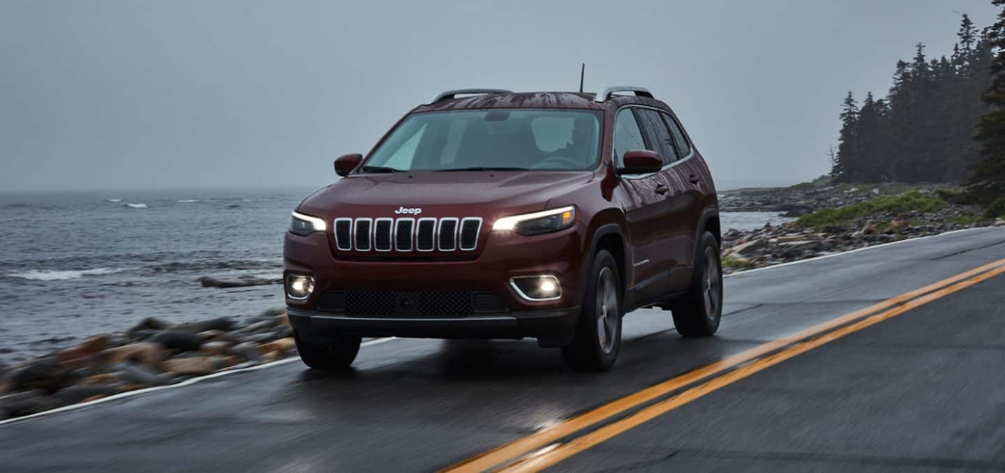 Display The 2021 Jeep Cherokee being driven on a two lane road beside a lake.