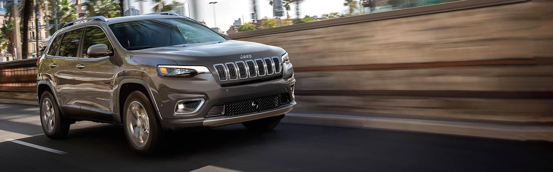 Un Jeep Cherokee Limited 2021 andando por una autopista junto a una barrera de sonido.