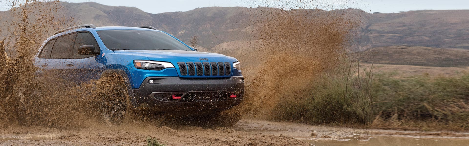 ElJeep Cherokee Trailhawk2021 andando por terreno fangoso, salpicando tierra desde sus ruedas.
