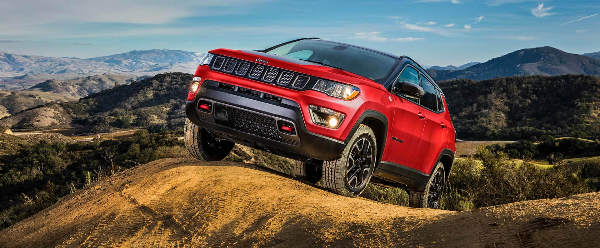 The 2021 Jeep Compass ascending a hill on a dirt track.