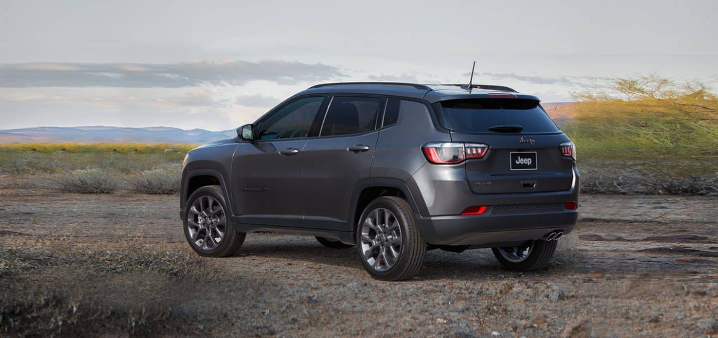 Display A three-quarter rear view of a 2021 Jeep Compass 80th Anniversary Edition parked on a sandy trail with mountains in the distance.