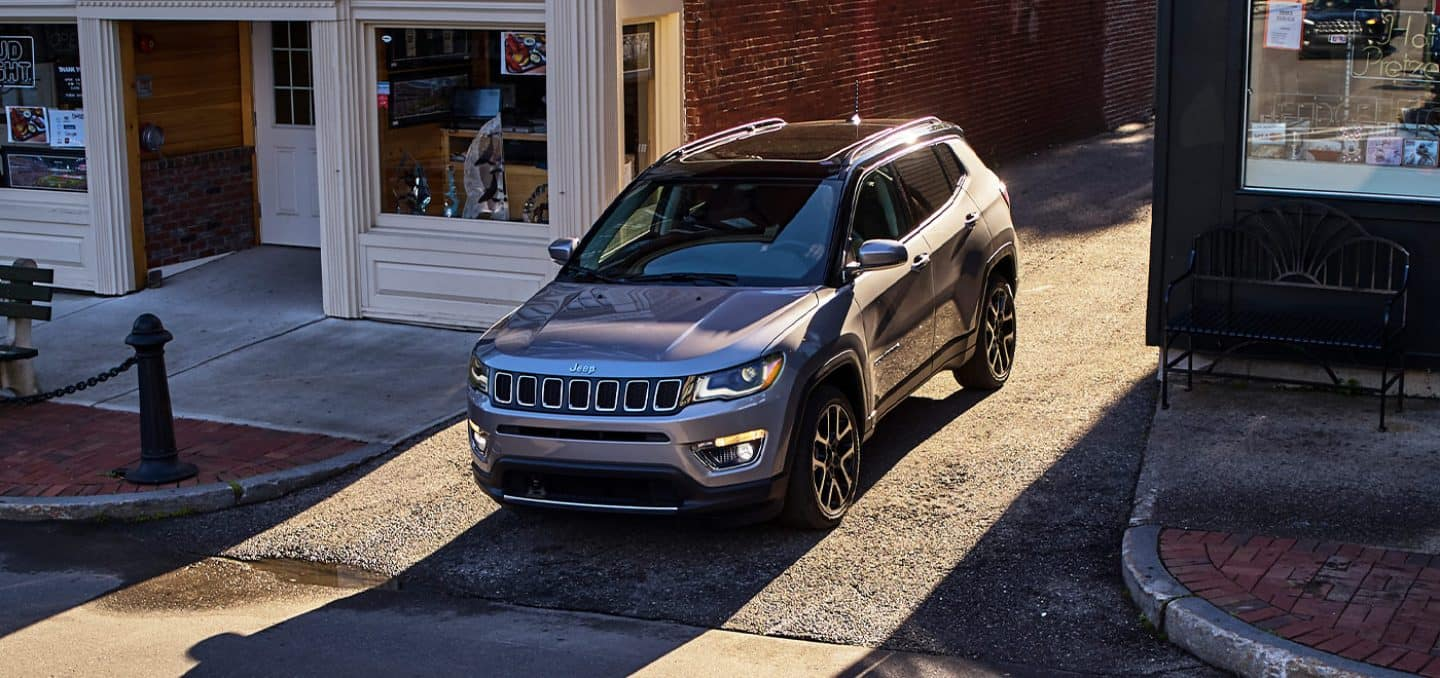 Display The 2021 Jeep Compass Limited being driven through an alley onto a city street.
