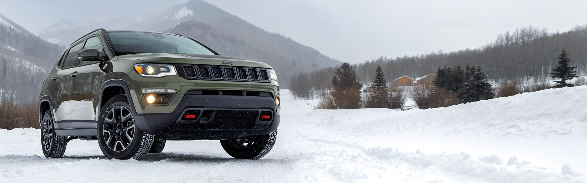 A three-quarter front view of a 2021 Jeep Compass Trailhawk being driven in snow.