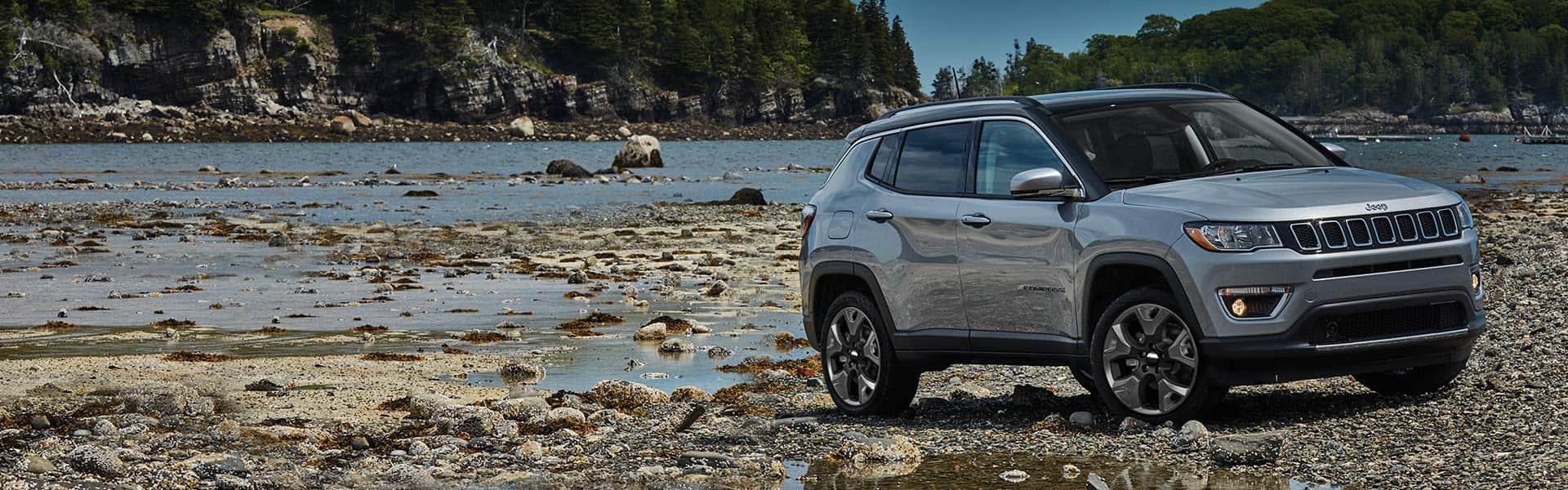 Un Jeep Compass Limited 2021 plateado estacionado sobre una costa rocosa rodeado de bosque.