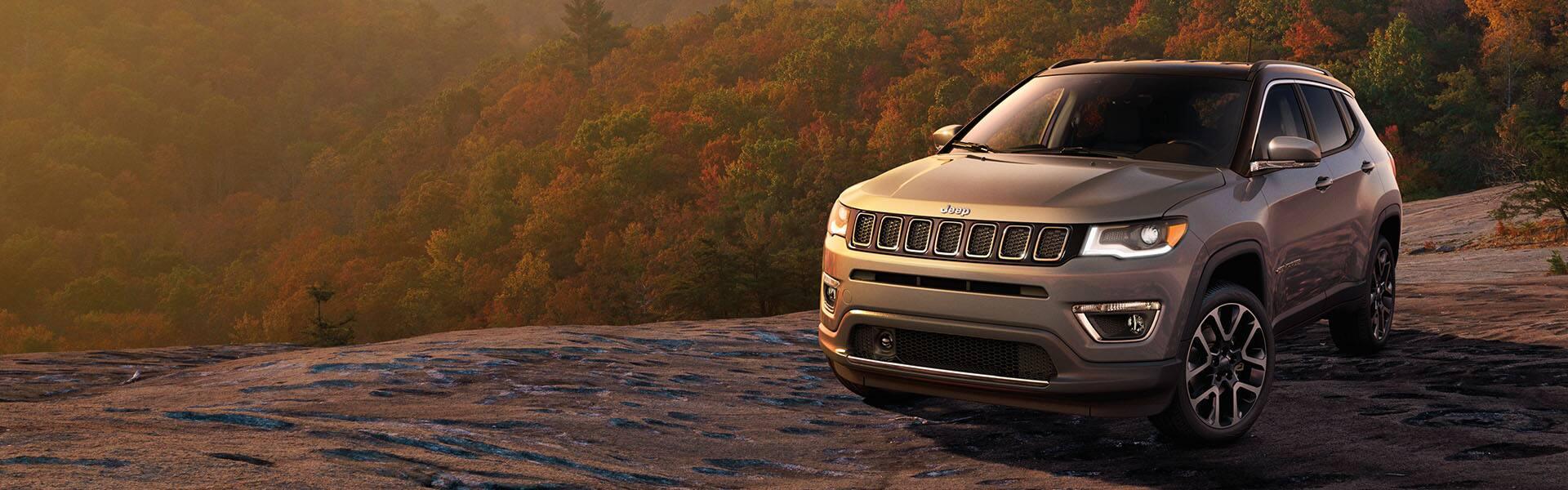 El Jeep Compass Limited 2021 estacionado al borde de un acantilado rocoso con vista a un valle con árboles cubiertos de follaje otoñal.