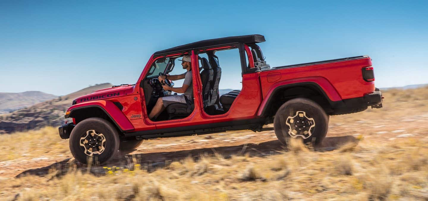 Display The 2021 Jeep Gladiator Rubicon being driven in a sandy field with all four doors removed.