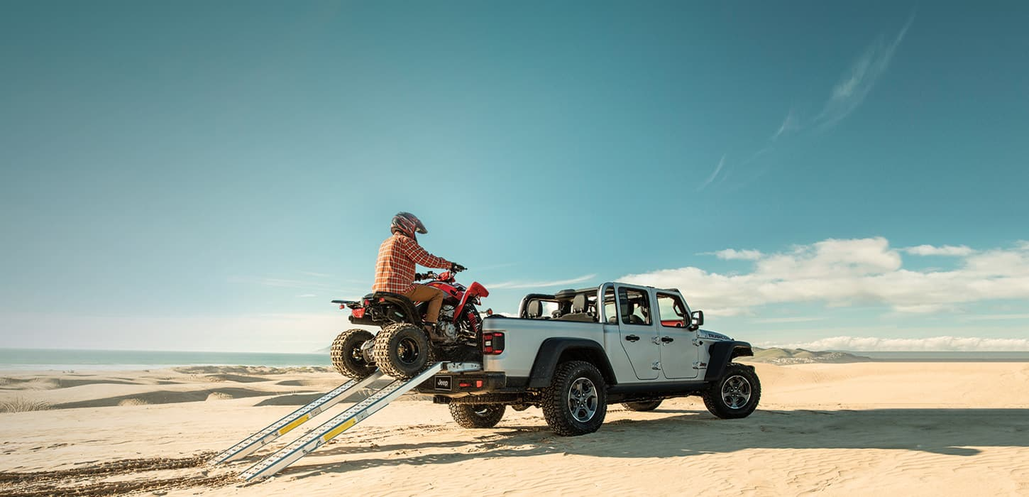 A man driving an ATV up a ramp into the bed of a 2021 Jeep Gladiator Rubicon.