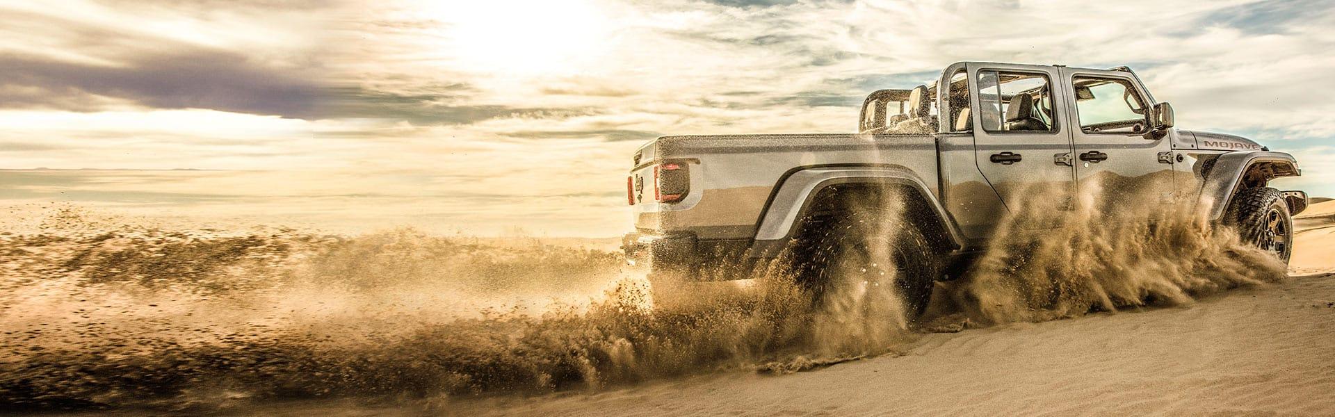 LaJeep Gladiator2021 levantando arena de sus ruedas mientras va por el desierto.