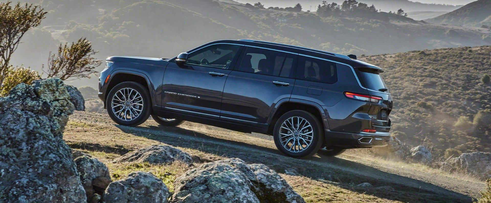 The 2021 Jeep Grand Cherokee L Summit Reserve parked facing uphill on a grassy track in the mountains.