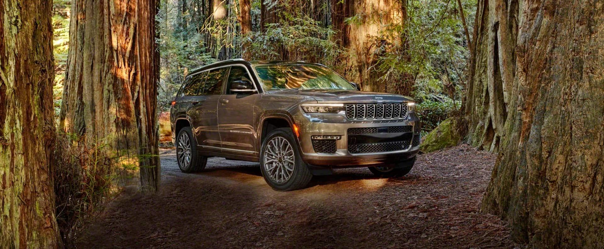 ElJeep Grand Cherokee L Summit Reserve2021 estacionado en un camino de tierra en un claro de bosque.
