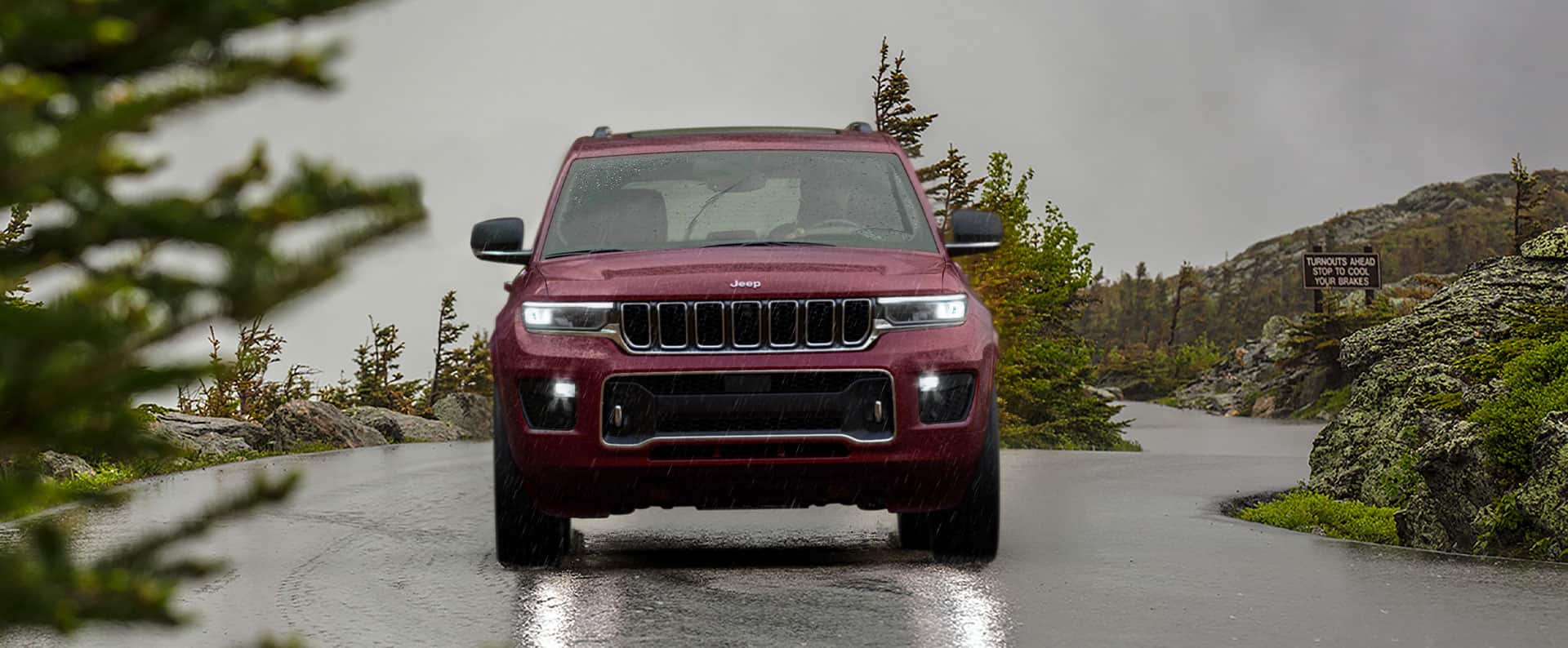 A head-on view of a 2021 Jeep Grand Cherokee L Overland being driven on a rain-slicked road.