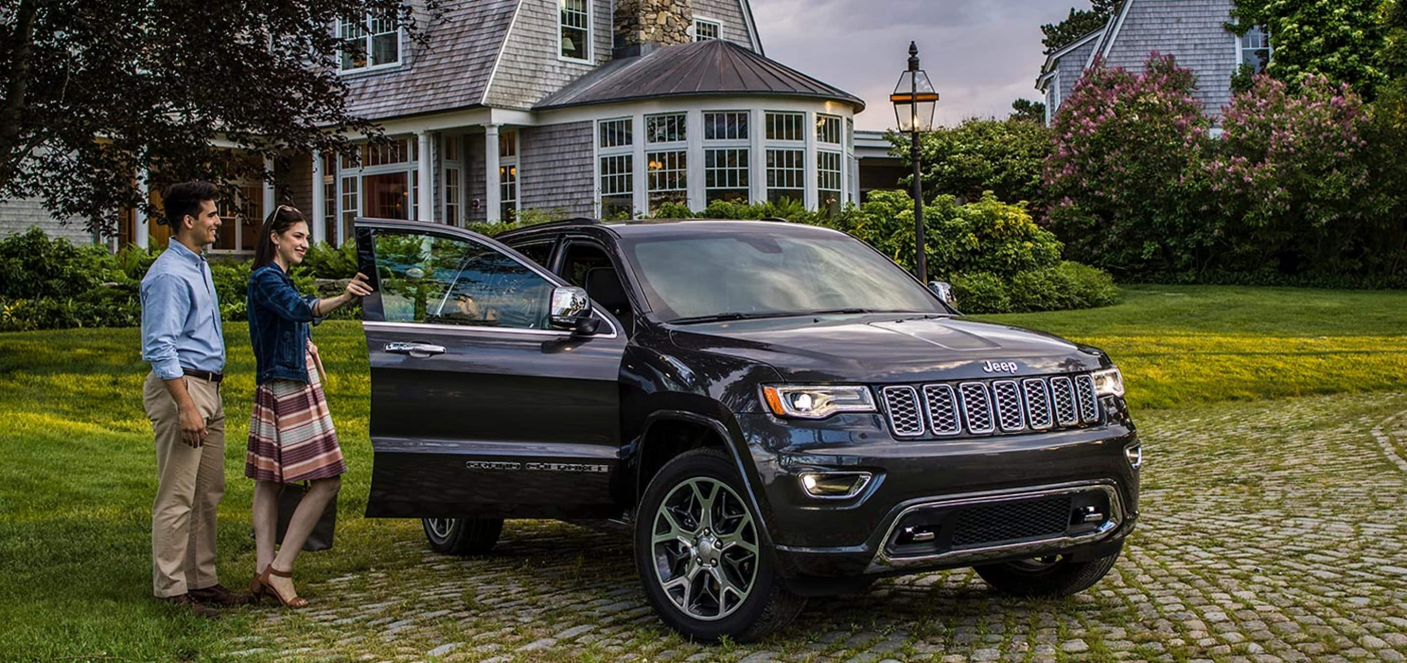 A couple opening the door of a black 2021 Jeep Grand Cherokee SUV parked outside their house