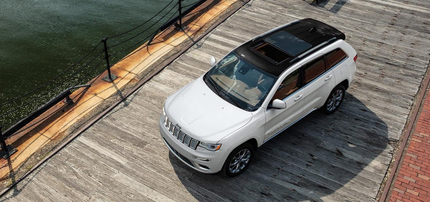 Display A bird's eye view of the 2021 Jeep Grand Cherokee Summit parked on a boardwalk beside the water.