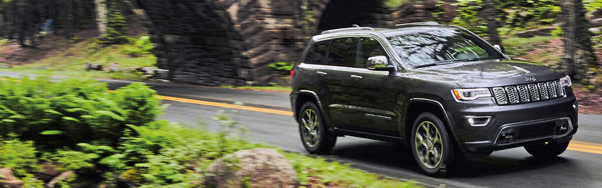 A 2021 Jeep Grand Cherokee Overland being driven on a highway through the woods, just past an old tunnel.